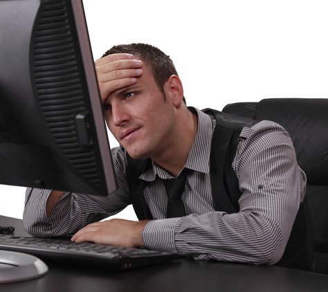 Unhappy young businessman in front of his computer at the office.